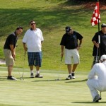 A caddy helping golf tournament participants with their putting. (San Diego, 2011)