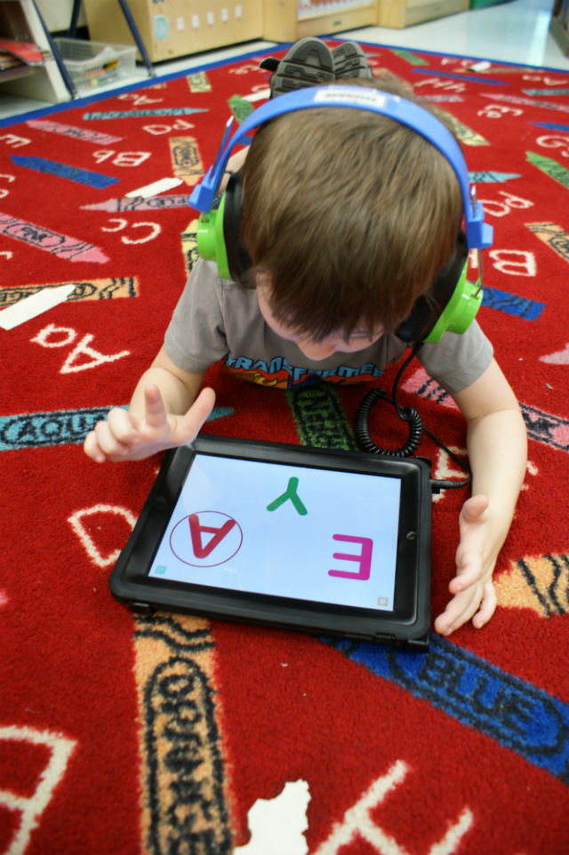 A young student at the Muskogee Early Childhood Center learning his alphabet on an iPad (Muskogee, 2011)