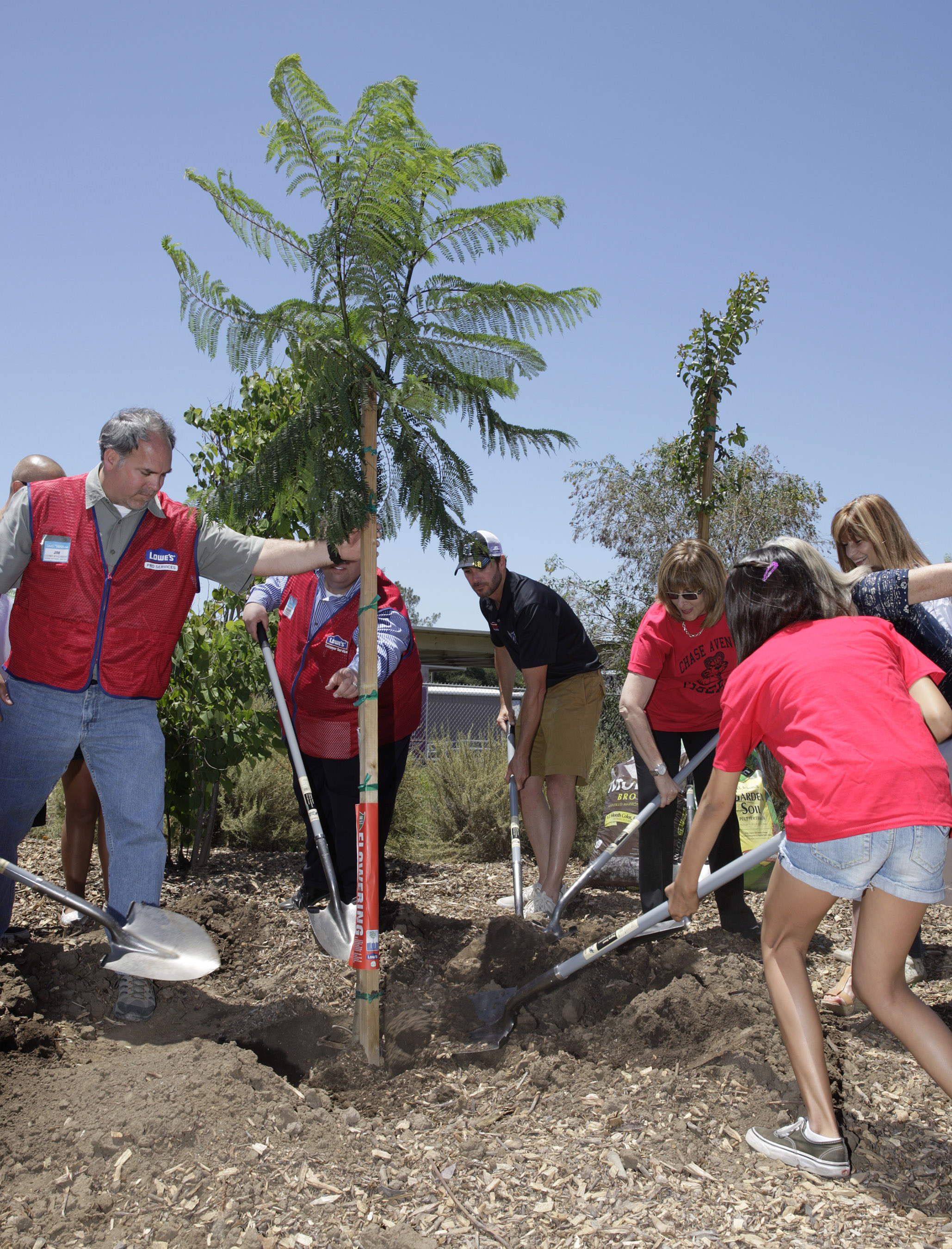 Jimmie, Lowe's Employees and Chase Avenue Elementary students plant trees during Jimmie's visit to the school. (El Cajon, 2013)